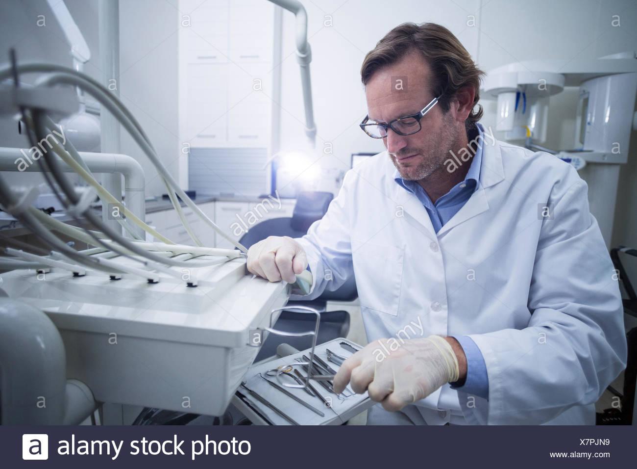 Dentista guardando strumento dentale Immagini Stock