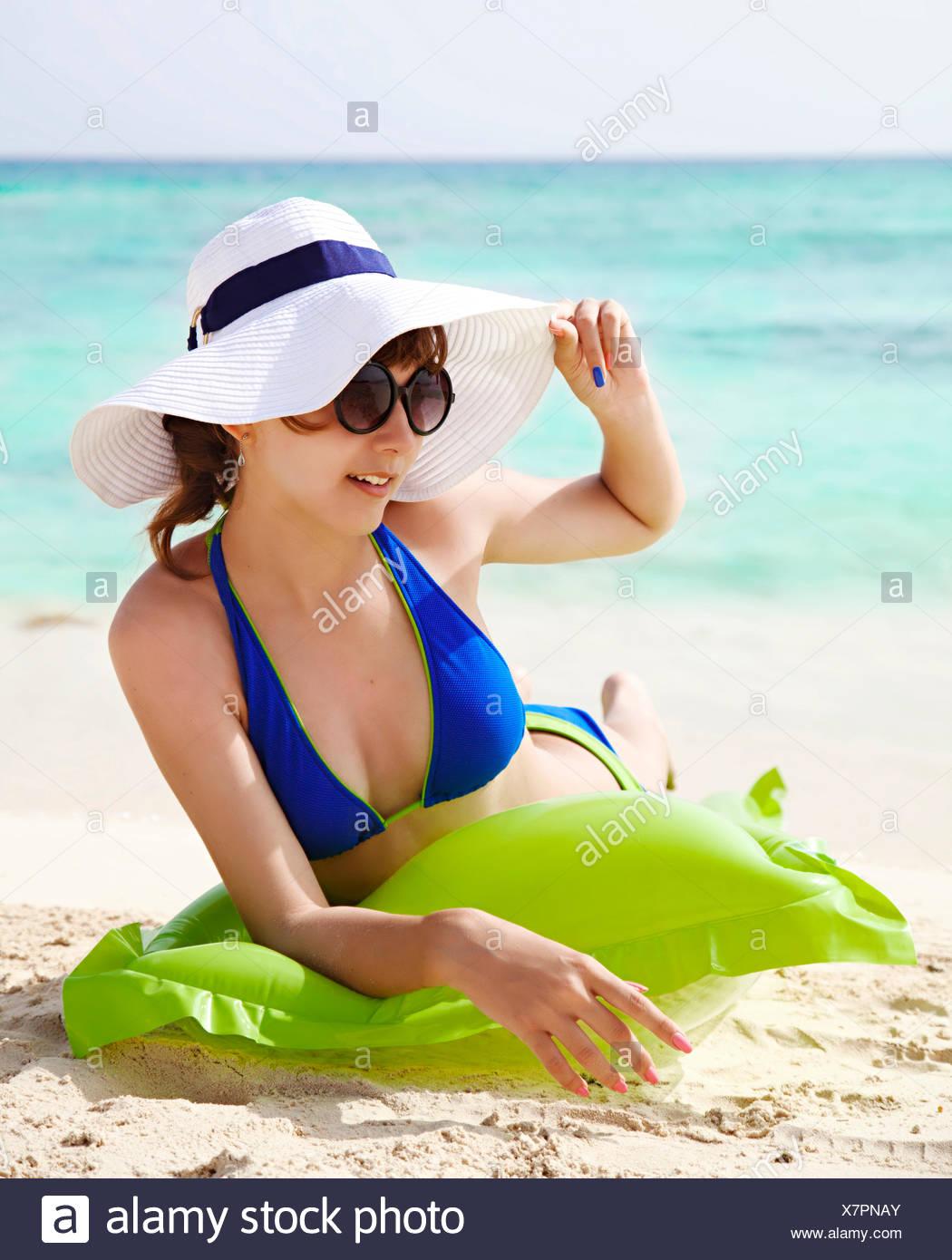 Ragazza adolescente in un bikini a prendere il sole sulla spiaggia Immagini Stock