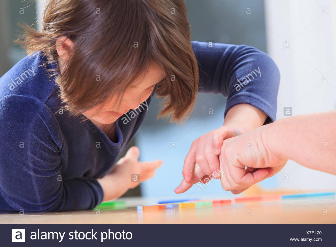 Bambina con la sindrome di Down la riproduzione di un gioco di apprendimento con la sua mamma Immagini Stock