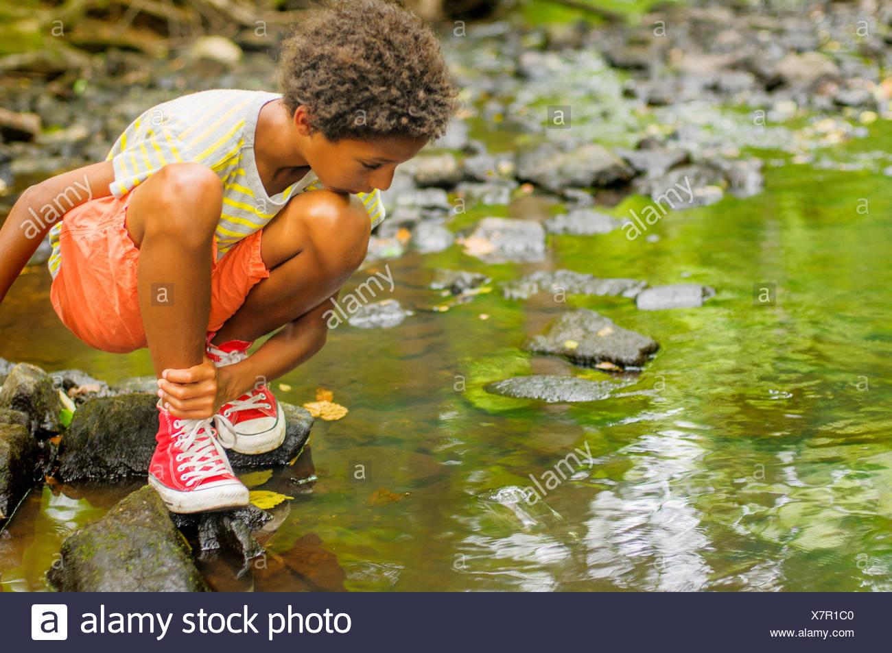 Ragazzo che guarda per pescare nel fiume Immagini Stock