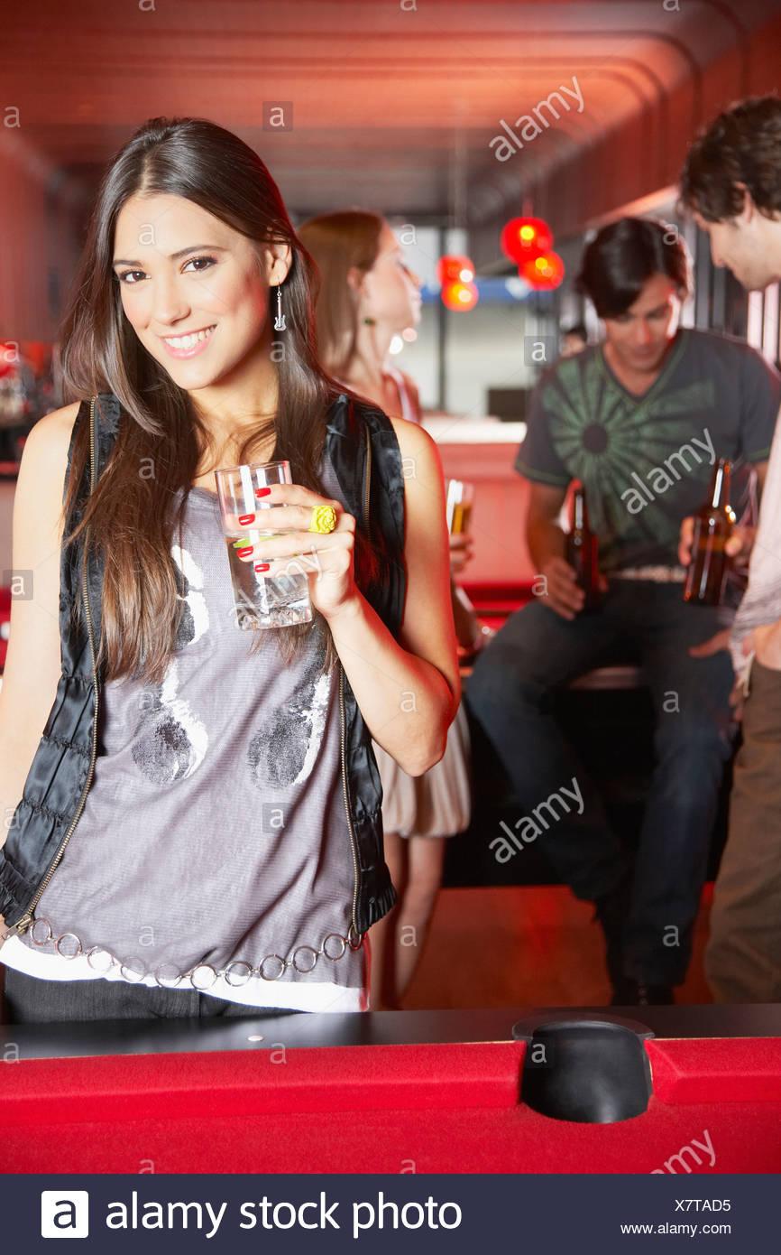 Donna con la bevanda in piedi da tavolo da biliardo sorridente Immagini Stock