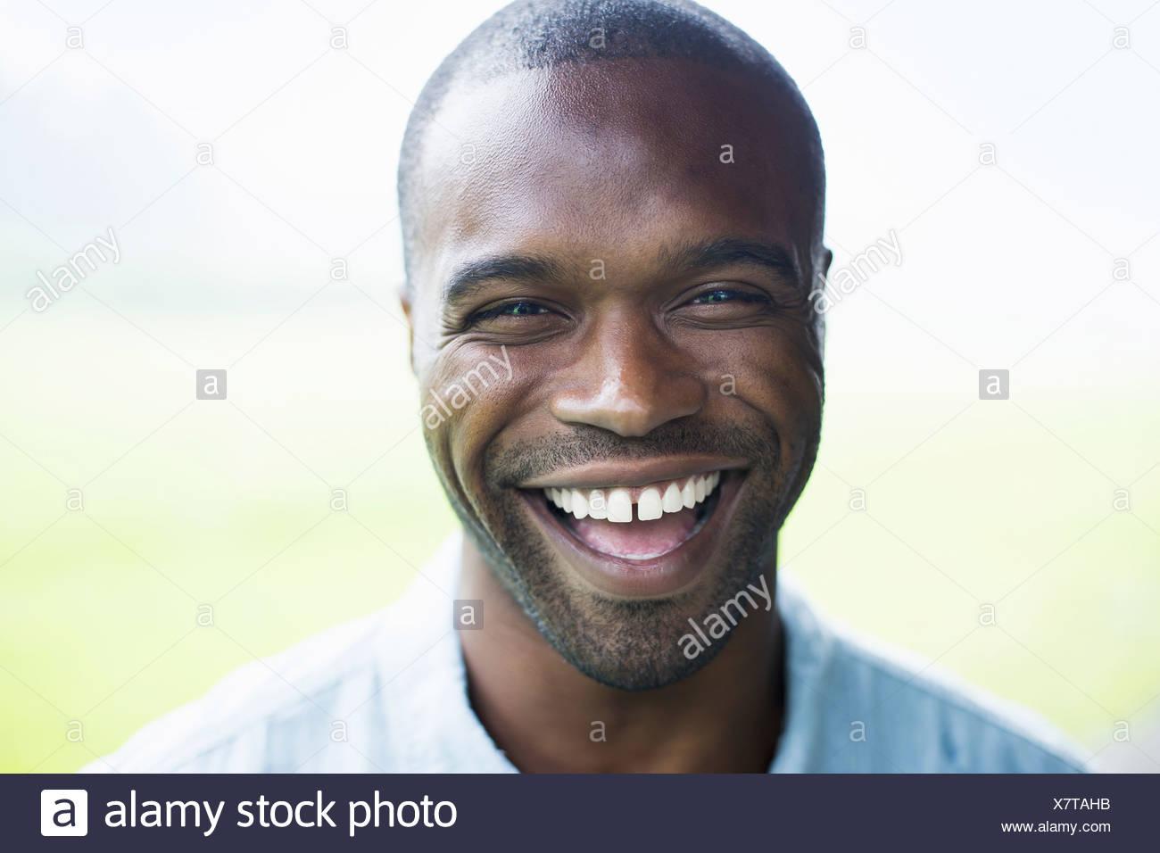 Un giovane uomo in una maglietta blu a ridere. Immagini Stock
