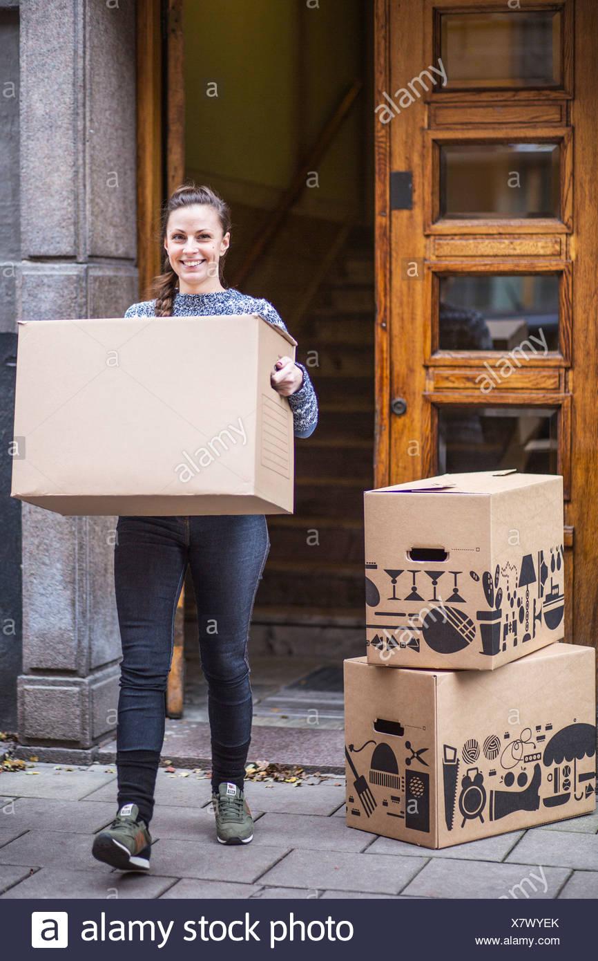 A piena lunghezza Ritratto di giovane donna con scatola di cartone camminando sul marciapiede Immagini Stock