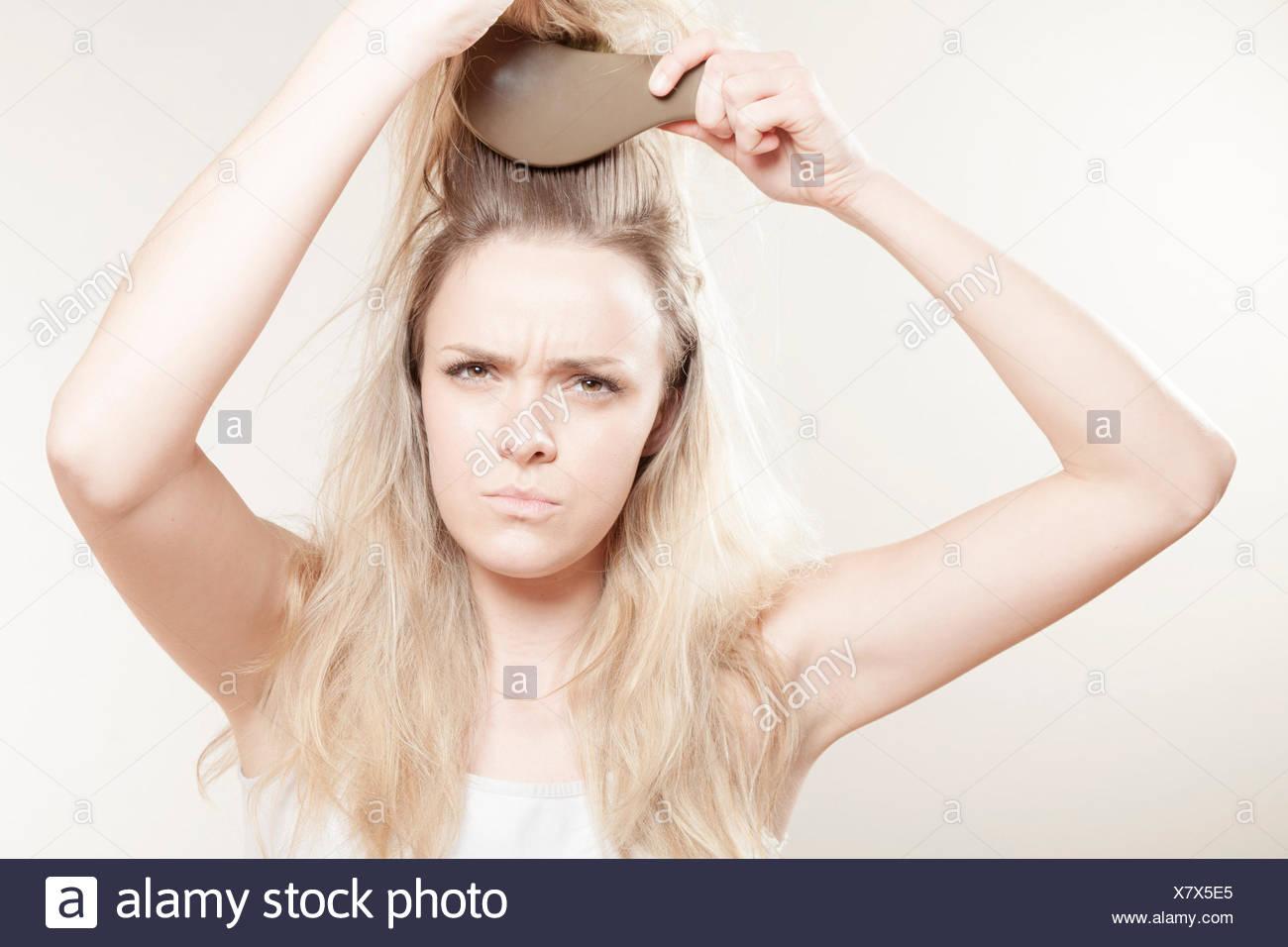 Giovane donna spazzolare i capelli Immagini Stock