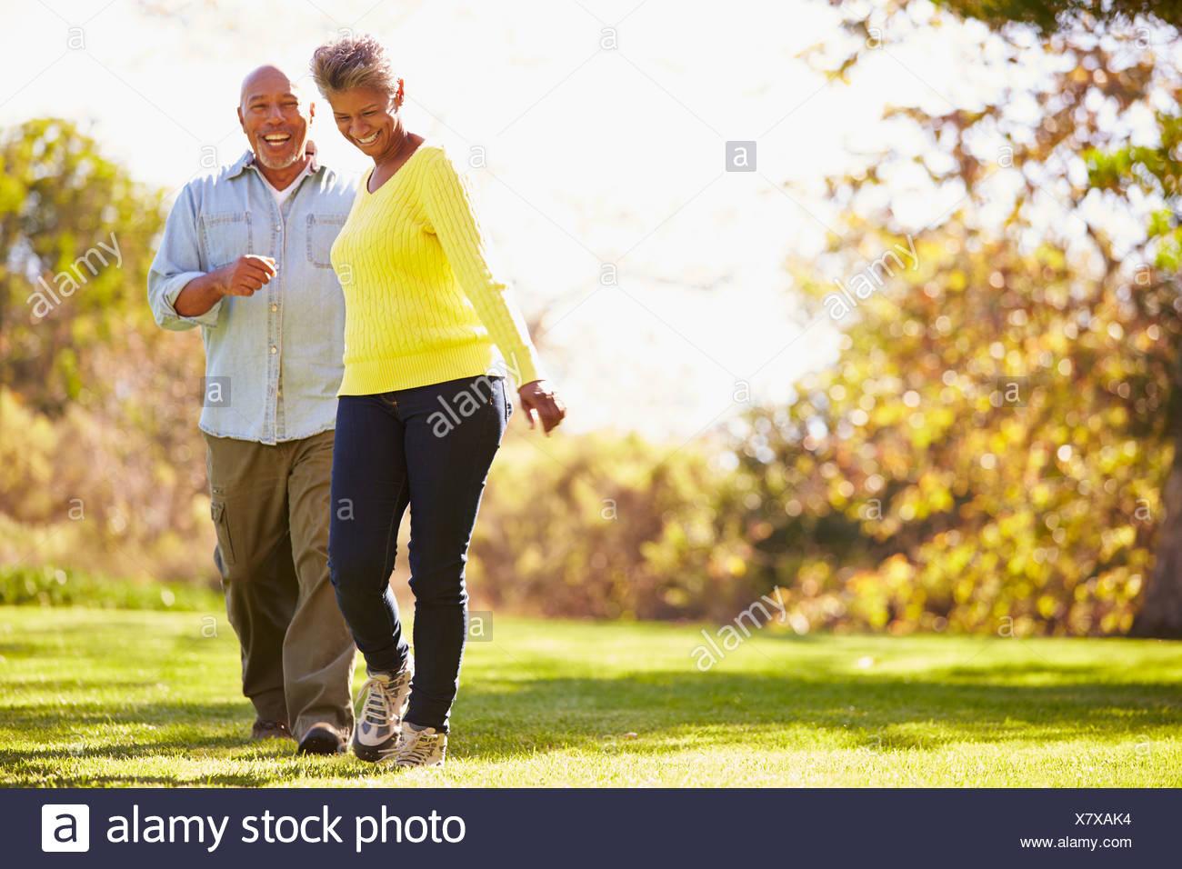 Coppia senior a piedi attraverso il bosco in autunno Immagini Stock