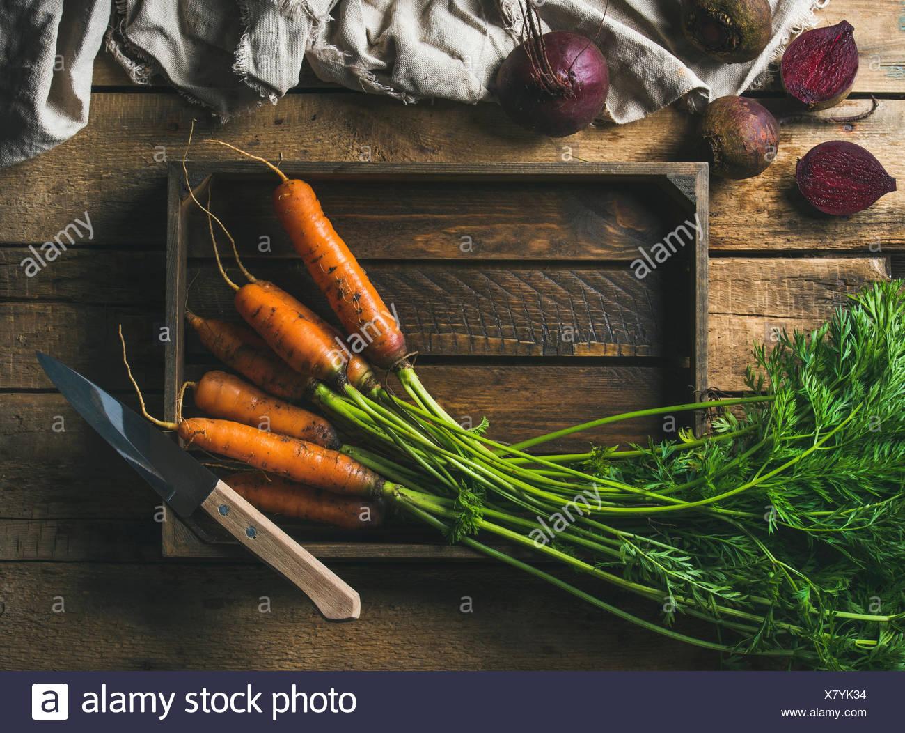 Cibo sano per la cottura dello sfondo. Di ingredienti vegetali. Fresco giardino carote e barbabietole nel vassoio in legno su legno rustico bac Immagini Stock