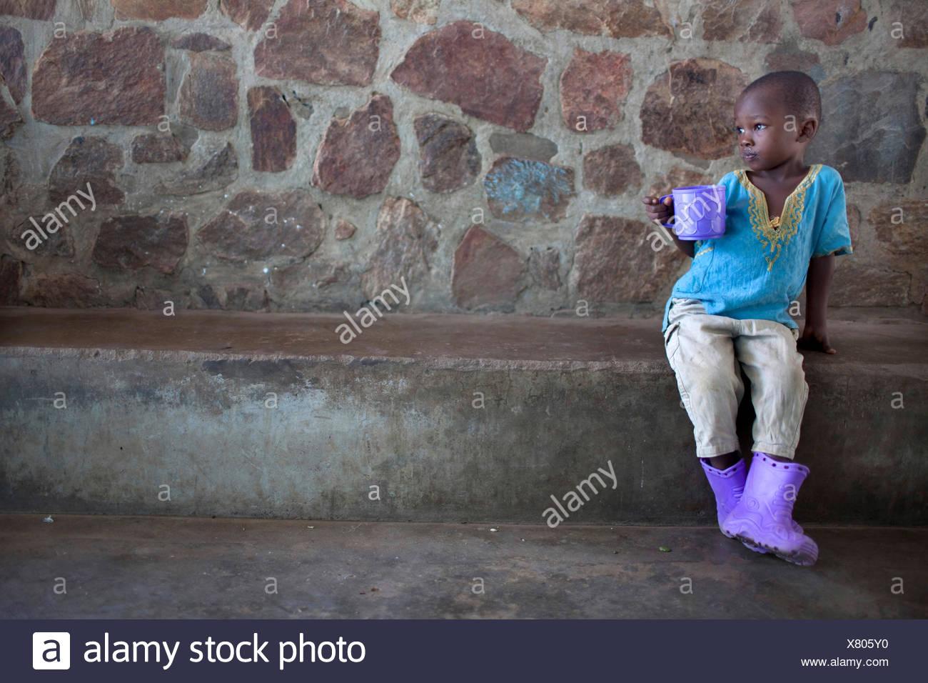 Ragazzino con coppa di porpora viola e stivali di gomma, Burundi Bujumbura Immagini Stock