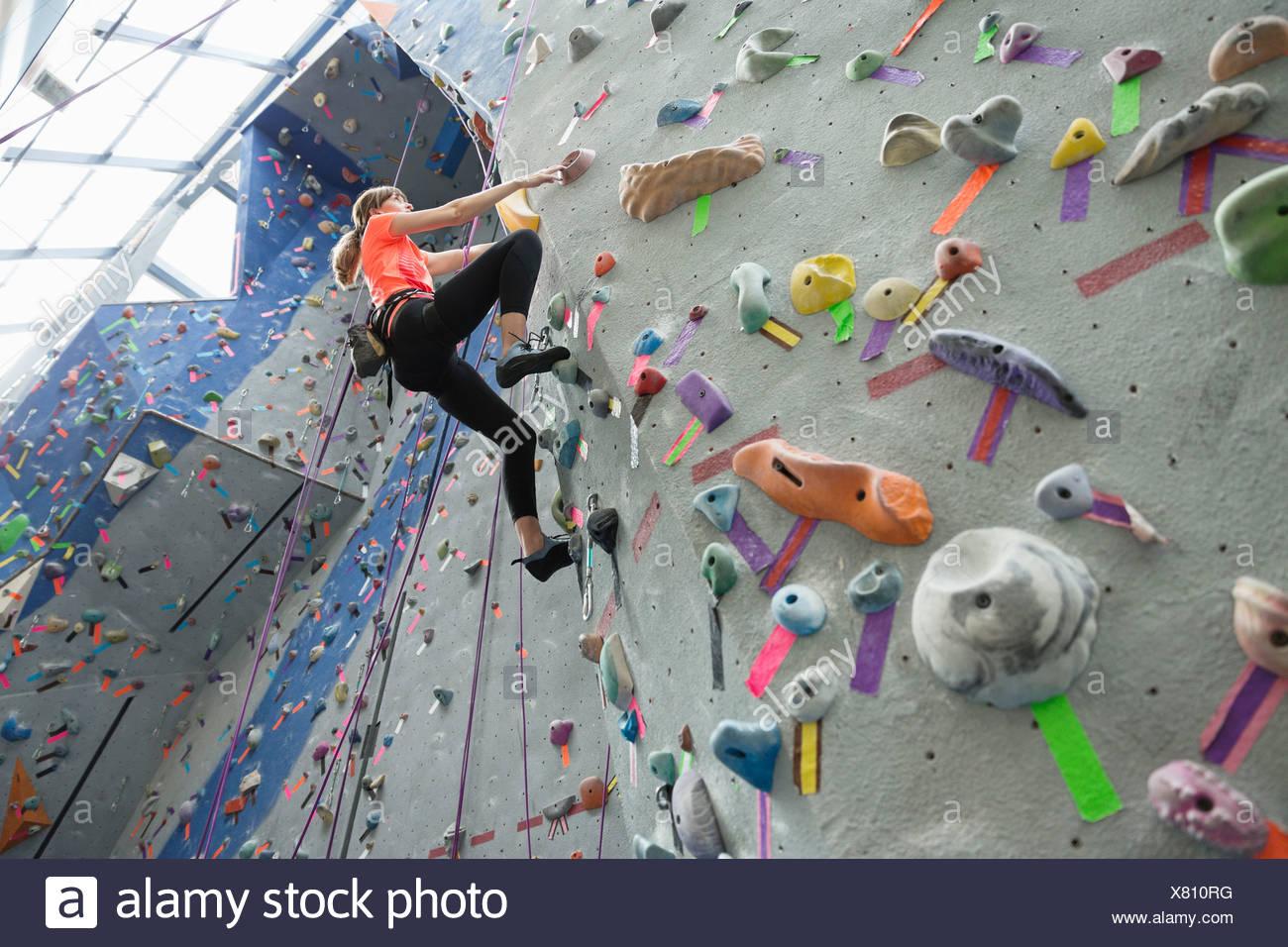 Basso angolo di visione della donna salendo sulla parete di arrampicata in palestra Immagini Stock