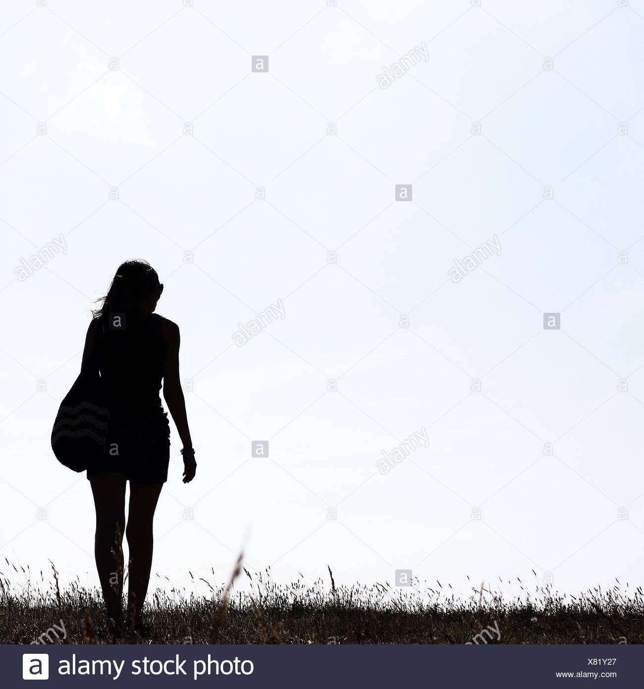 Silhouette di una ragazza in piedi all'aperto Immagini Stock
