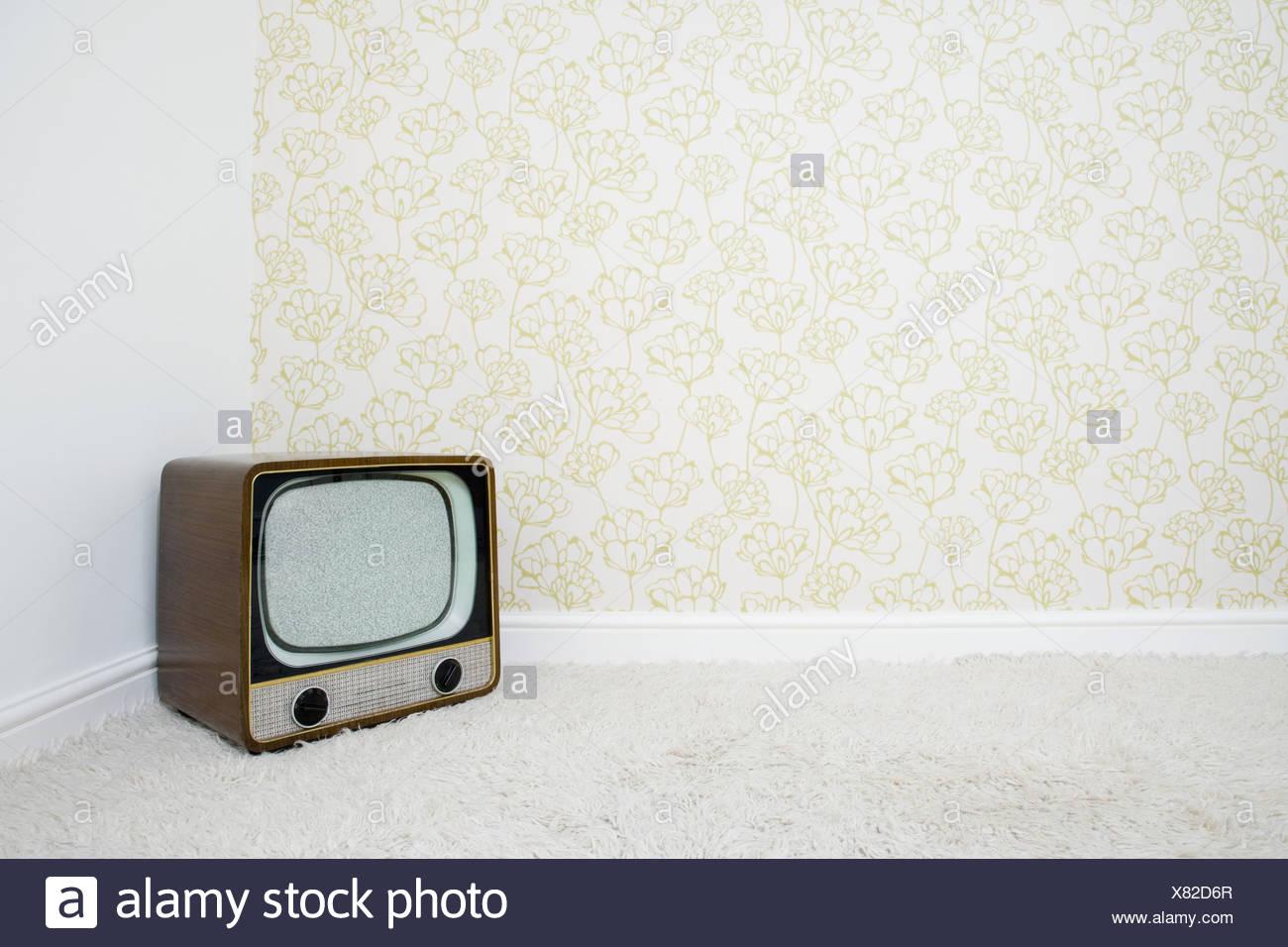 Televisione retrò in un angolo della stanza con carta da parati Immagini Stock