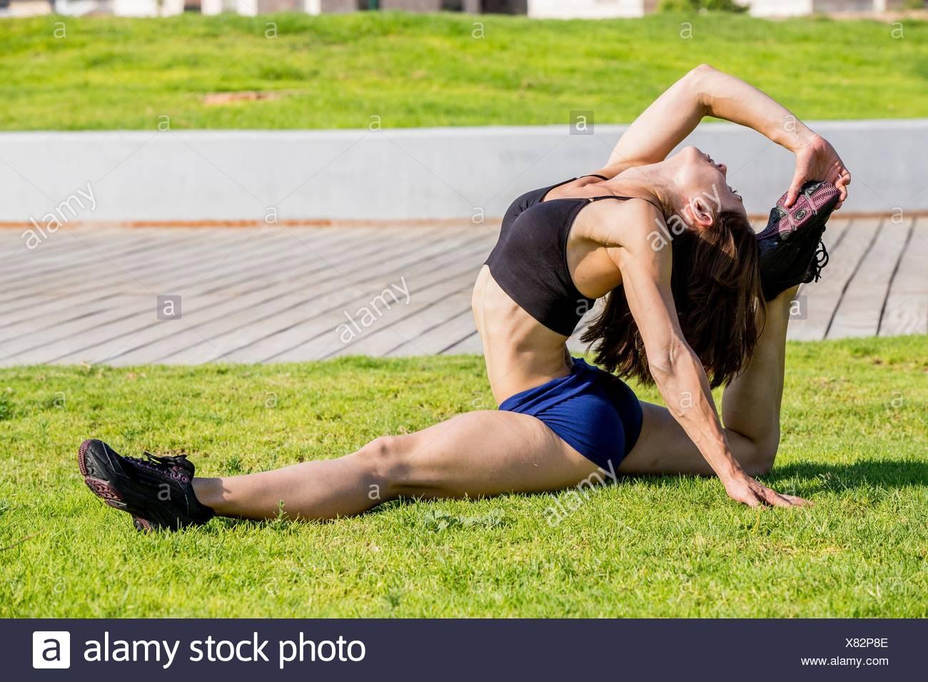 Giovane donna facendo si estende in posizione di parcheggio Immagini Stock