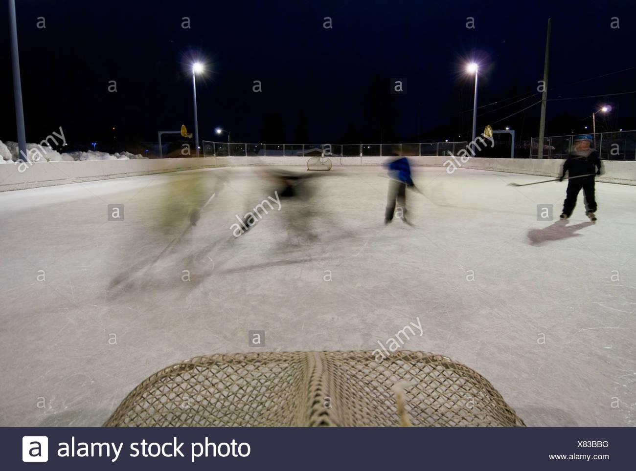 Una famiglia gioca un gioco di pick-up hockey presso la locale scuola elementare la pista di pattinaggio su ghiaccio in Anchorage in Alaska,. Immagini Stock
