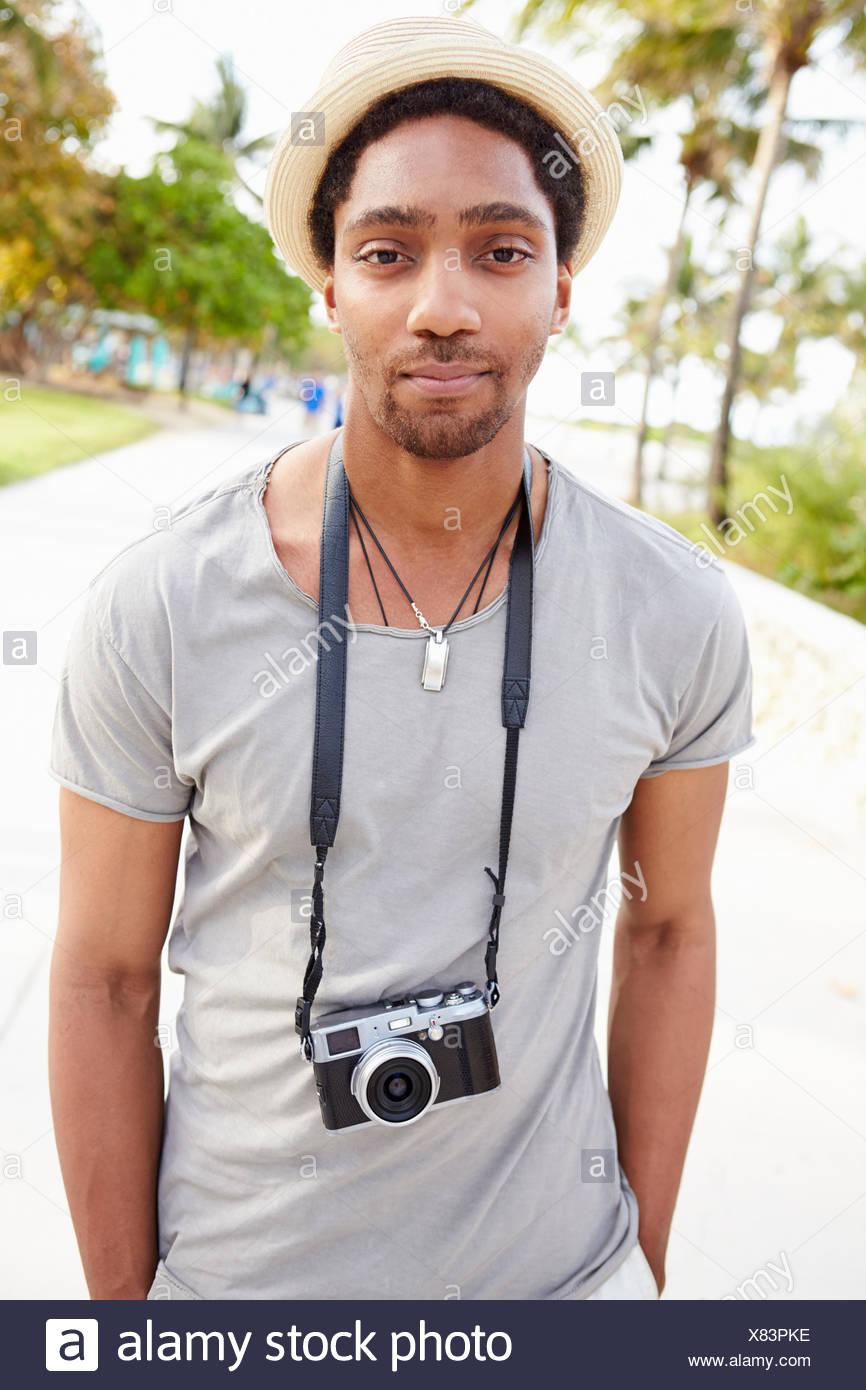 Ritratto di giovane uomo che porta la fotocamera Immagini Stock