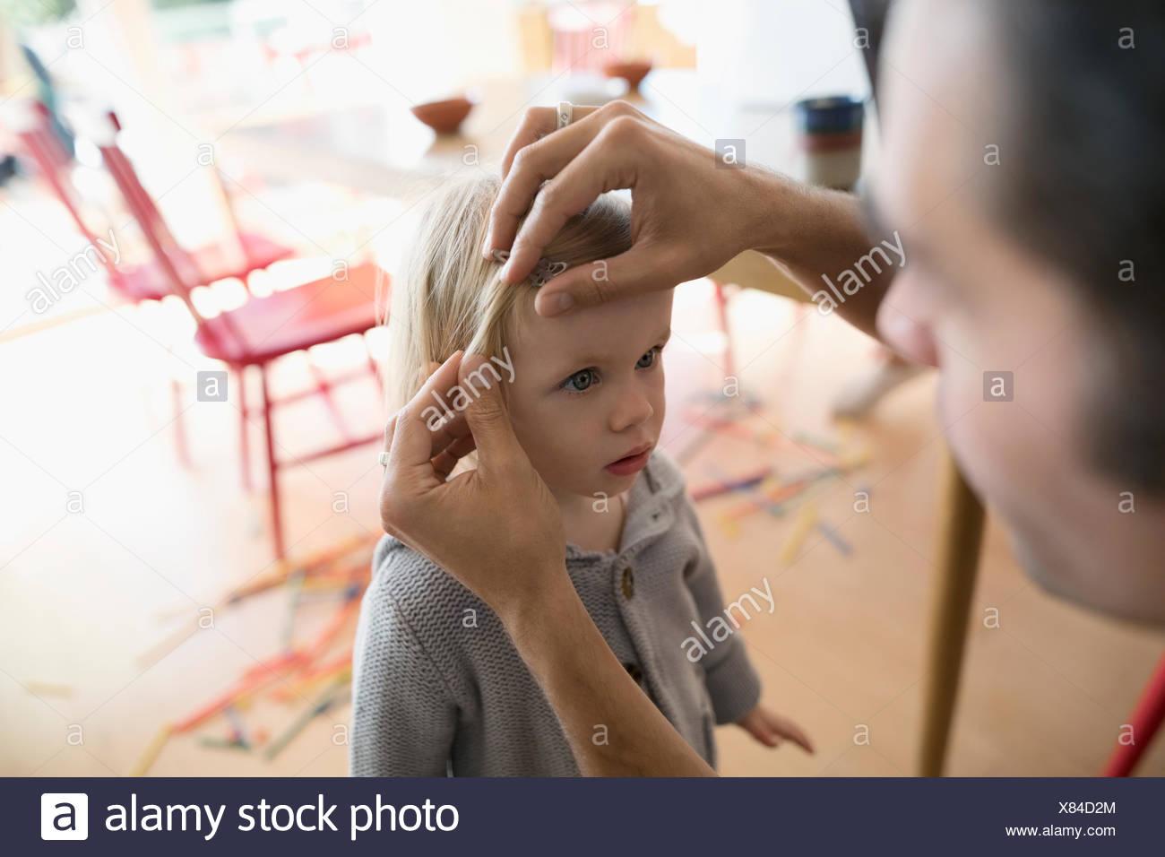 Padre che fissa il toddler figlie capelli Immagini Stock