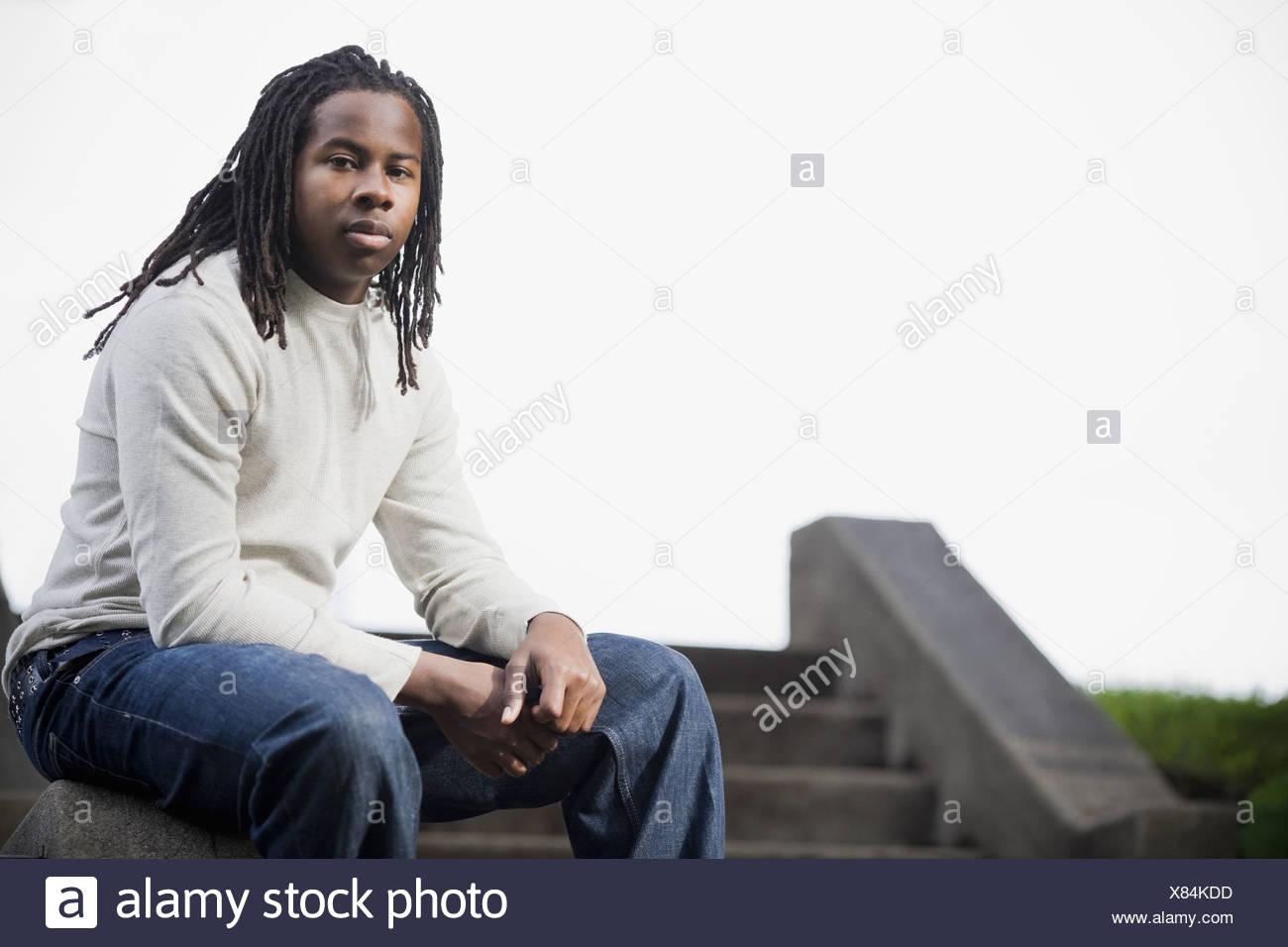 Ritratto di ragazzo adolescente (16-17) con Dreadlocks, seduti sui gradini Foto Stock