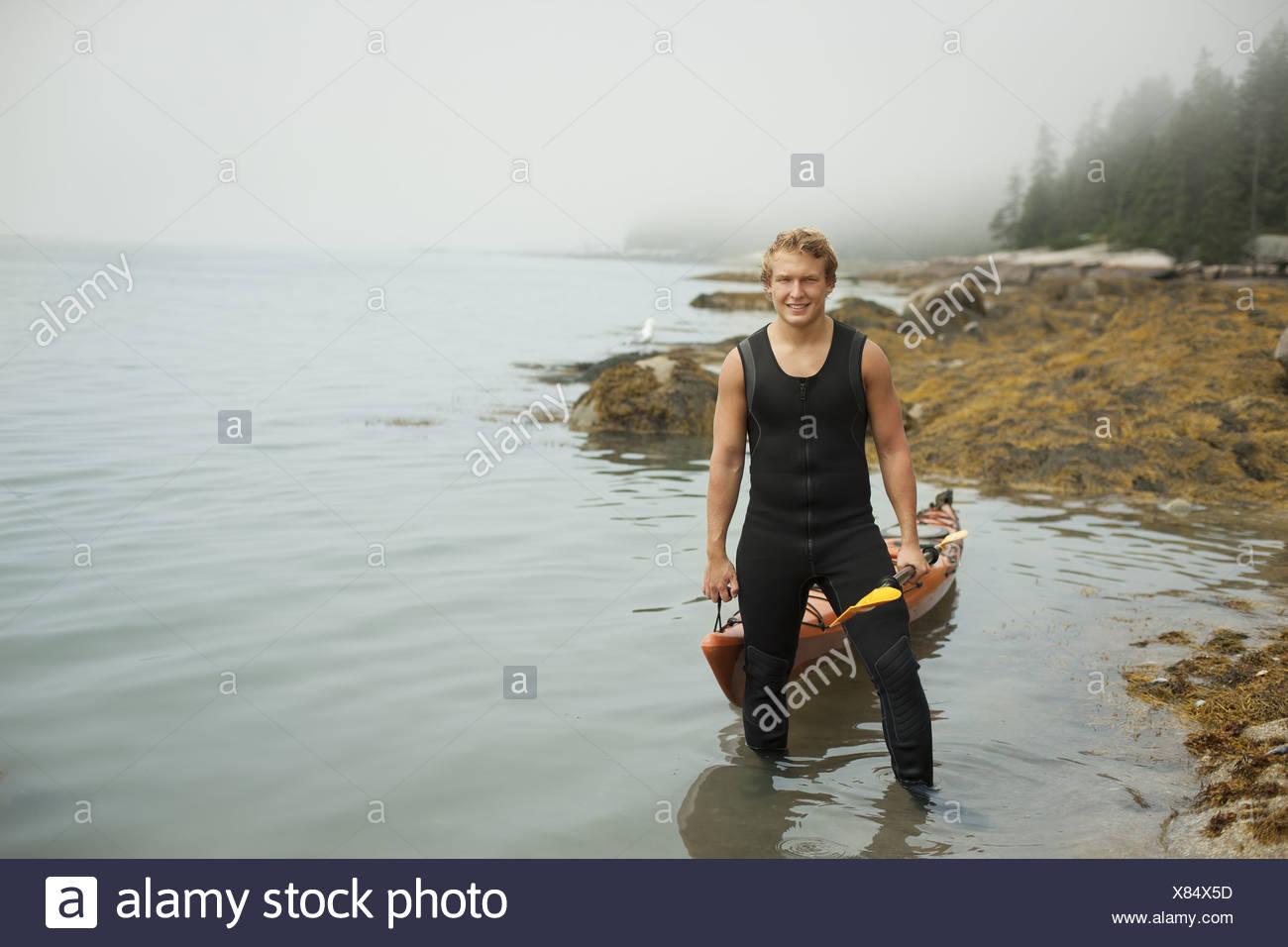 Lo stato di New York STATI UNITI D'AMERICA uomo muta kayak sul litorale di misty meteo Immagini Stock
