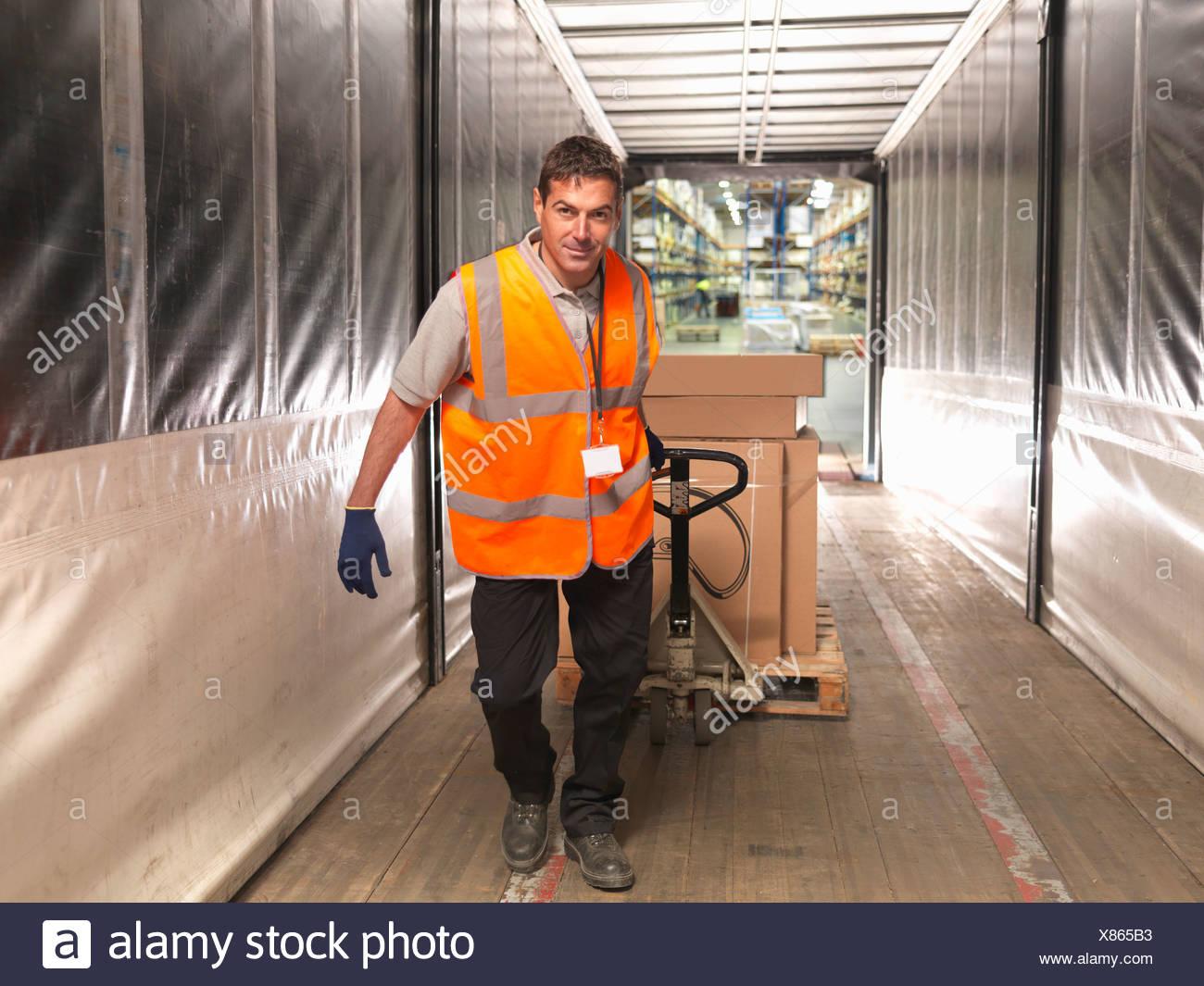 Carichi di lavoratore carrello elevatore con il carrello per movimentazione pallet Immagini Stock