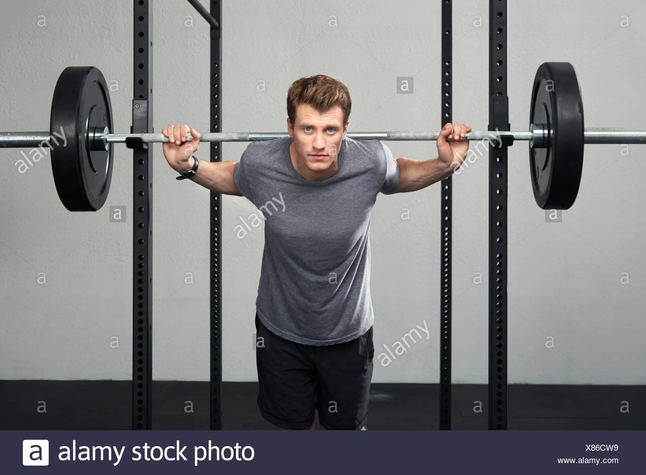 Ritratto di metà maschio adulto weightlifter sollevamento barbell in palestra Immagini Stock