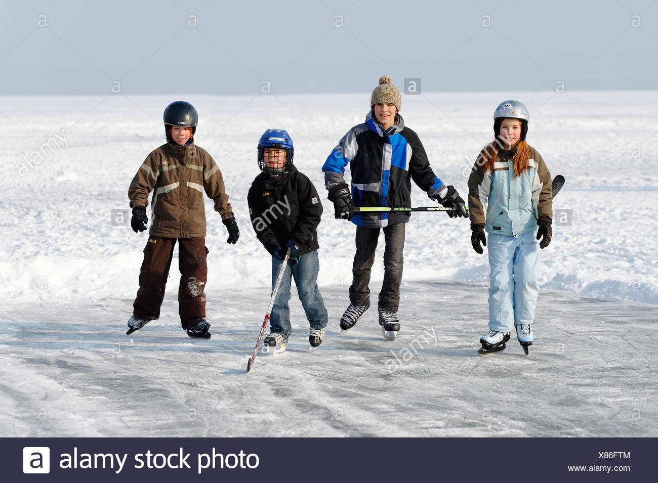Bambini che giocano hockey su ghiaccio, vicino San Heinrich, il lago di Starnberg, cinque laghi, Alta Baviera, Baviera Immagini Stock