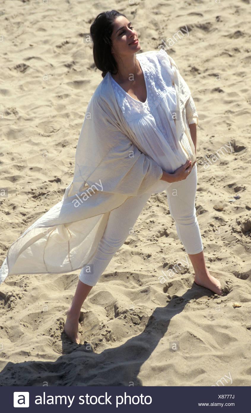 8616179c30c5 Ritratto di anglo-asian donna incinta in bianco che scorre vestiti  permanente sulla spiaggia sabbiosa