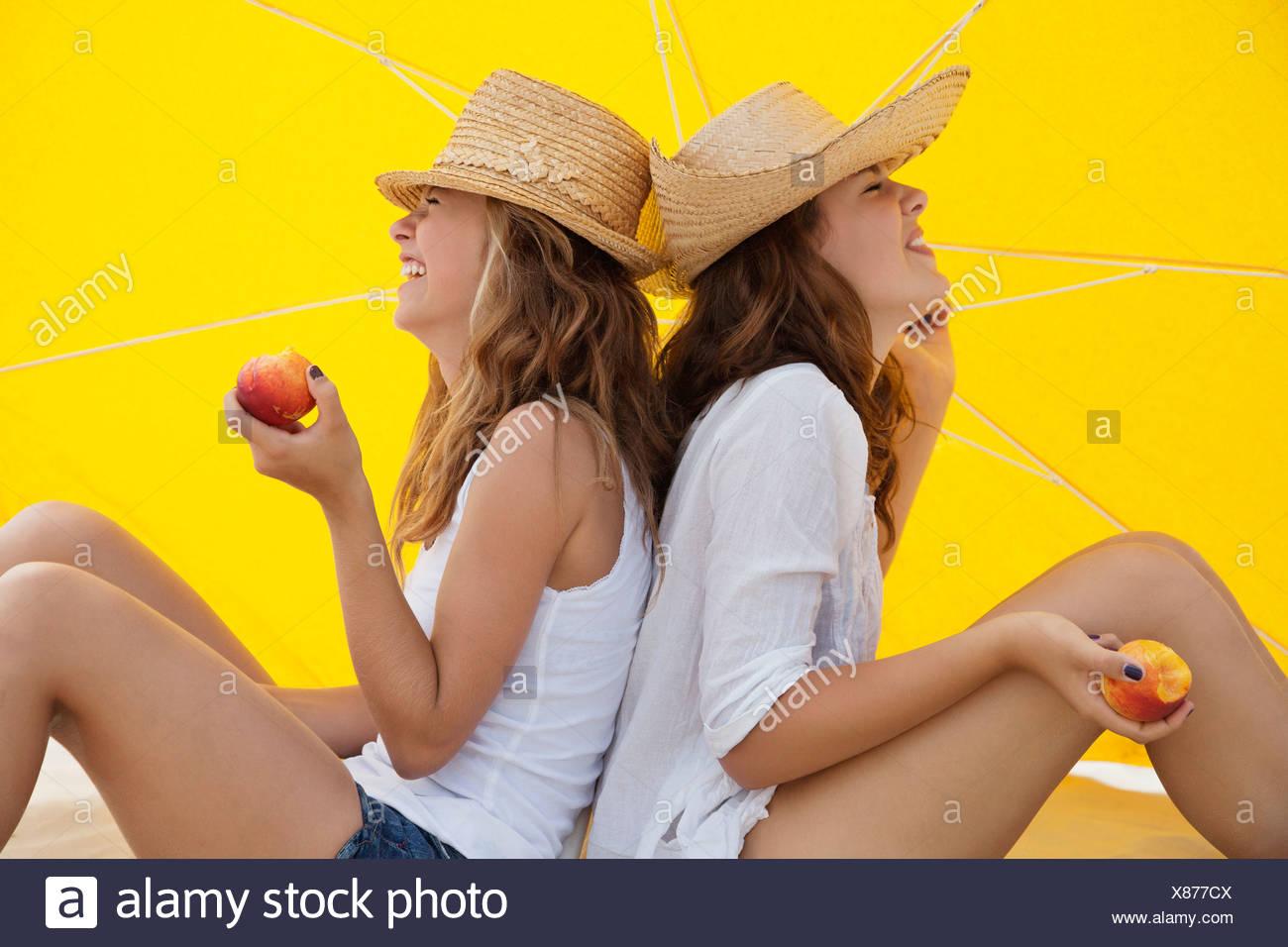Happy amici mangiando frutta in ombra Immagini Stock