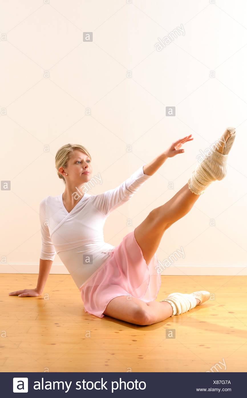 Bellissima ballerina braccio di sollevamento verso la gamba Immagini Stock