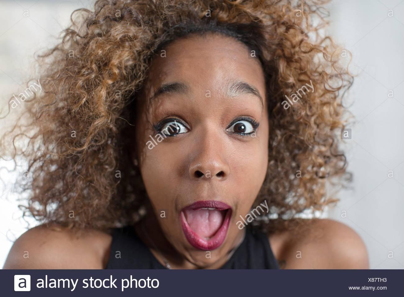 Ritratto di giovane donna tirando una faccia con la bocca aperta Foto Stock