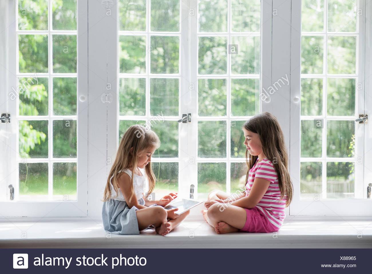 Due ragazze giocando, la condivisione di una tavoletta digitale. Immagini Stock