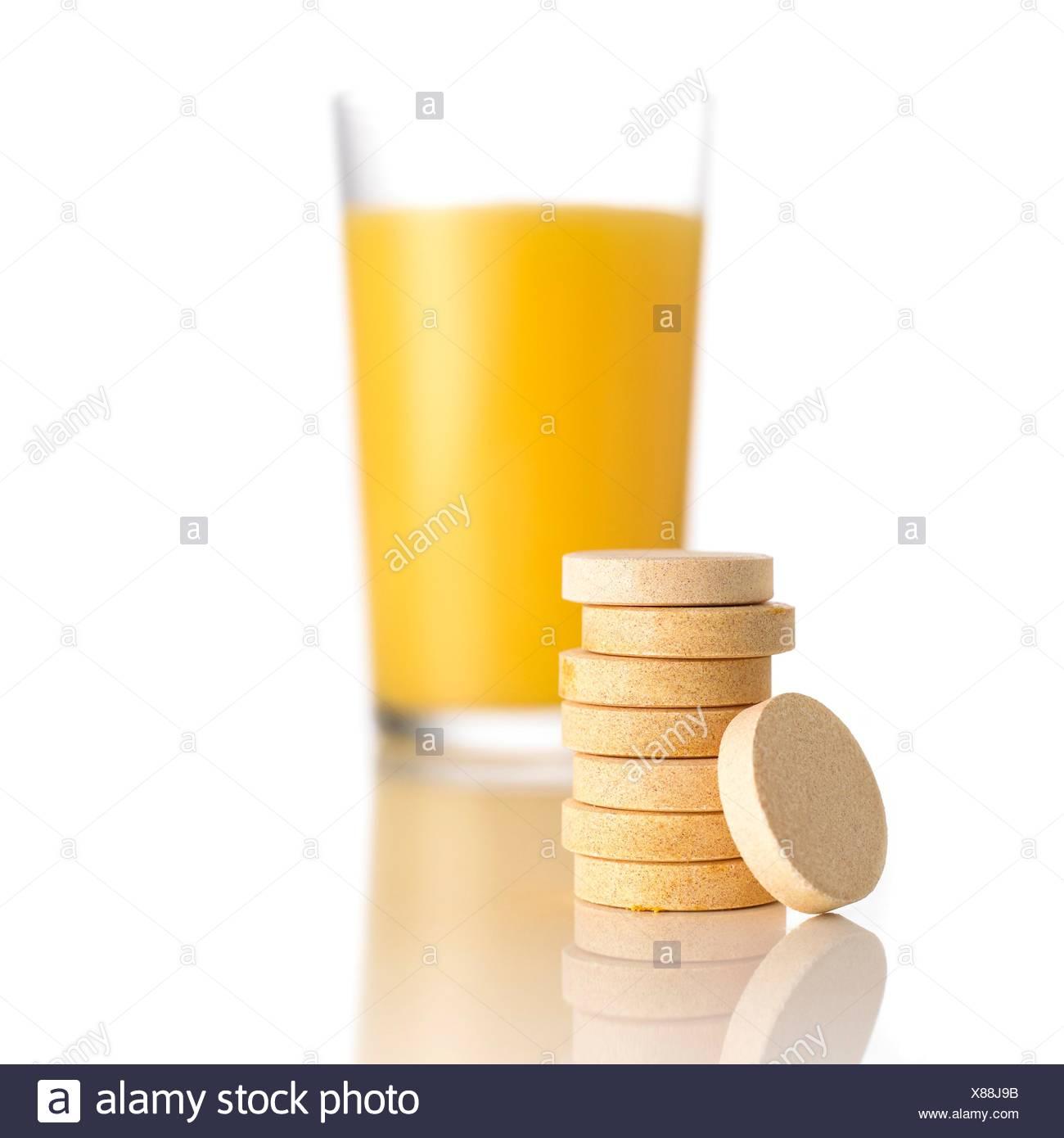 Succo di arancia e vitamina c compresse contro uno sfondo bianco. Immagini Stock