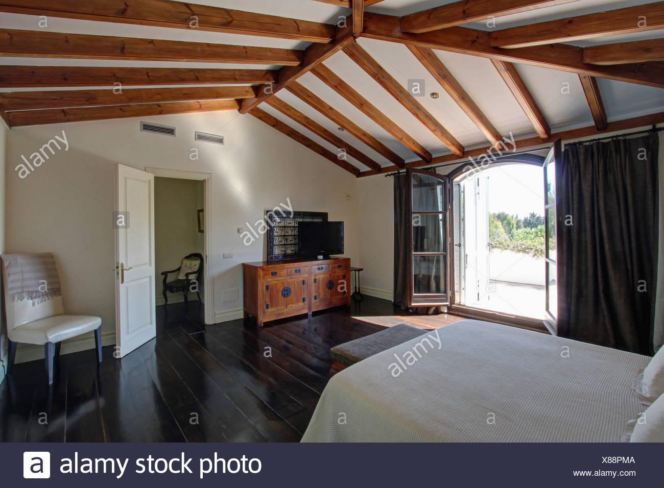 Foto Di Soffitti Con Travi In Legno : Lucido pavimento in legno scuro in spagnolo camera da letto con