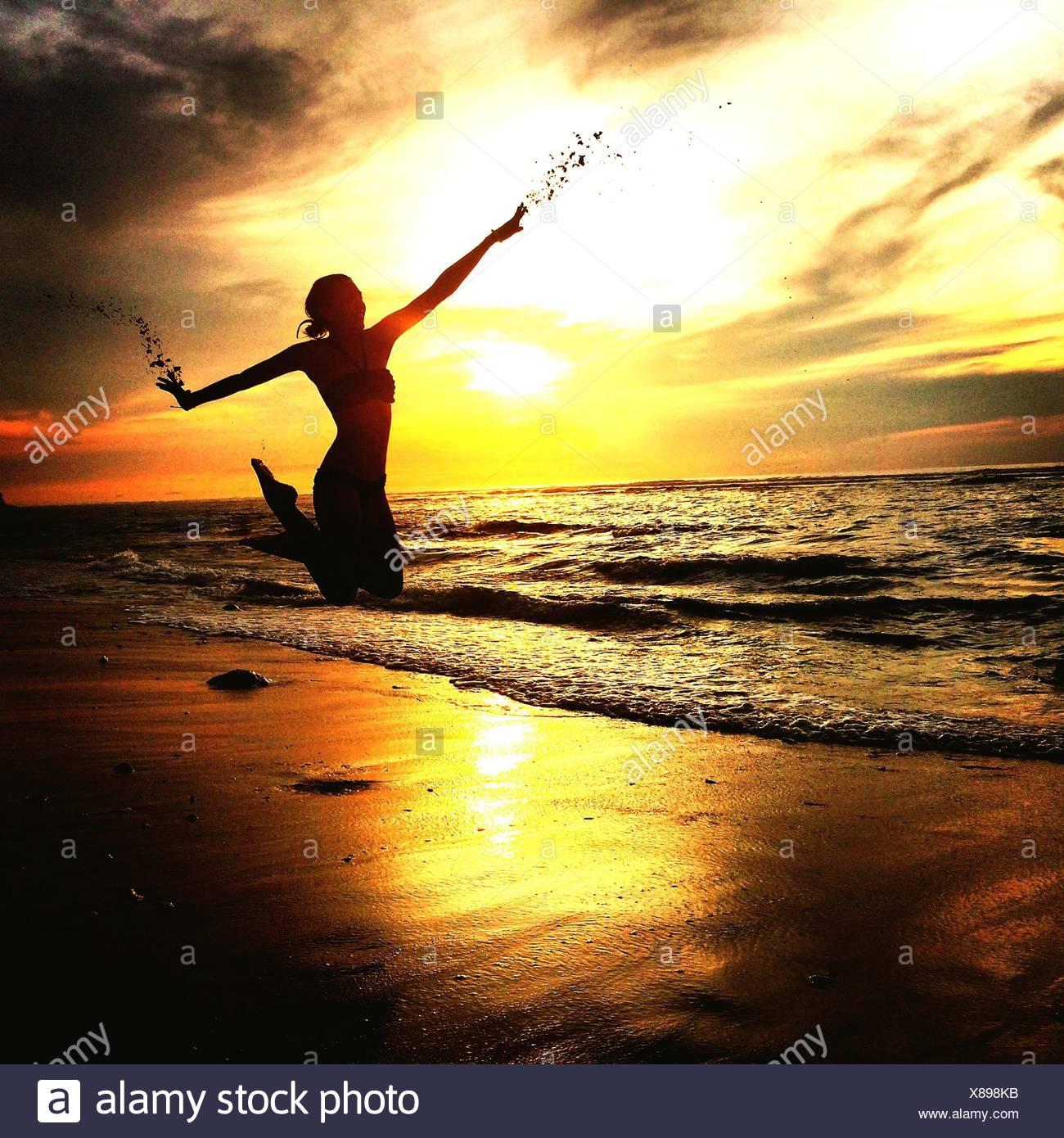 Donna salta sulla spiaggia di sabbia durante il tramonto Immagini Stock