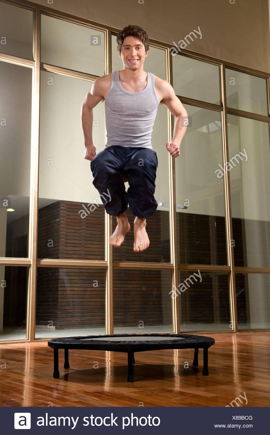 Uomo che indossa una maglietta a maniche corte grigia e pantaloni neri saltando su un trampolino elastico gommoso Foto Stock