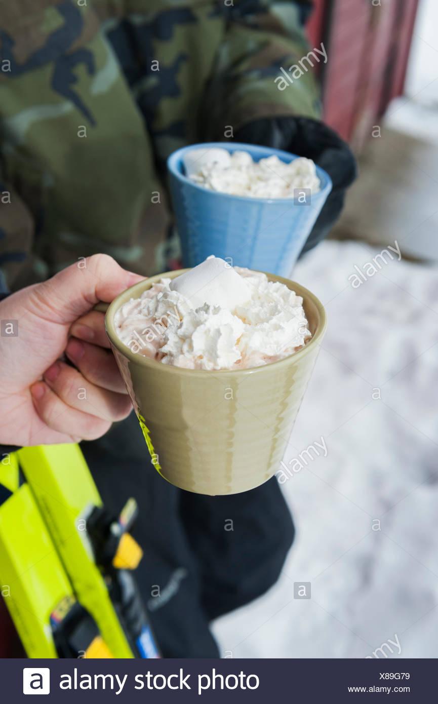 La Svezia, Stoccolma, Bjorkhagen, Hammarbybacken, vista ritagliata di un uomo e di una donna azienda tazze di cioccolata calda con panna montata Immagini Stock