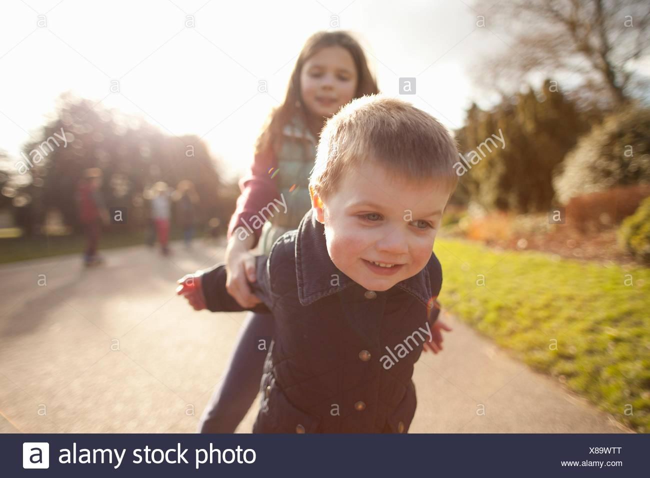 Ragazzo e la sorella a giocare nel parco Immagini Stock