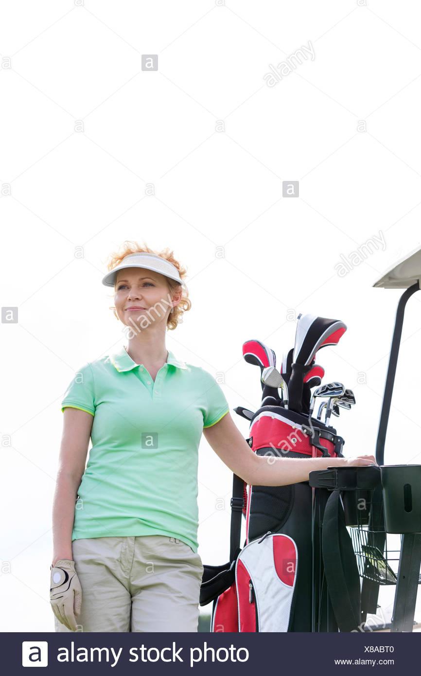 Basso angolo vista del golfista sorridente in piedi contro il cielo chiaro Immagini Stock