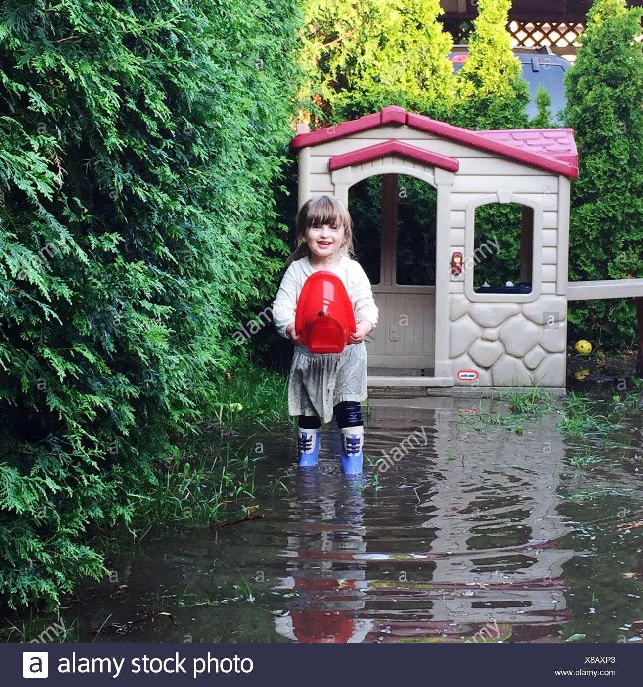 Ritratto di ragazza sorridente in piedi sul campo inondato Immagini Stock