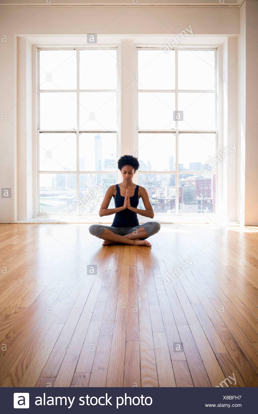 La donna a praticare yoga in camera Immagini Stock