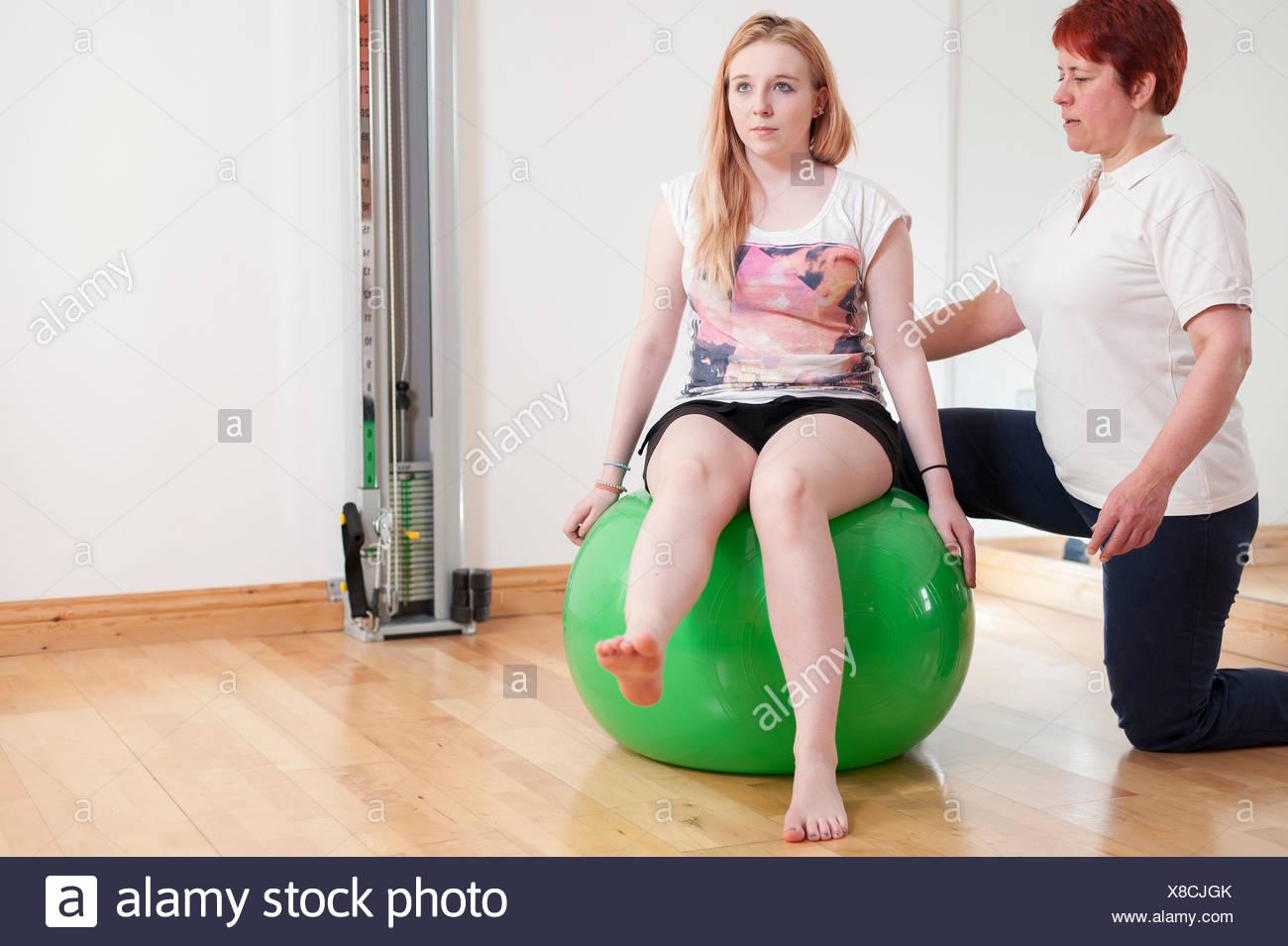 Giovane donna seduta sulla sfera di fitness, essendo guidato da donna matura Immagini Stock