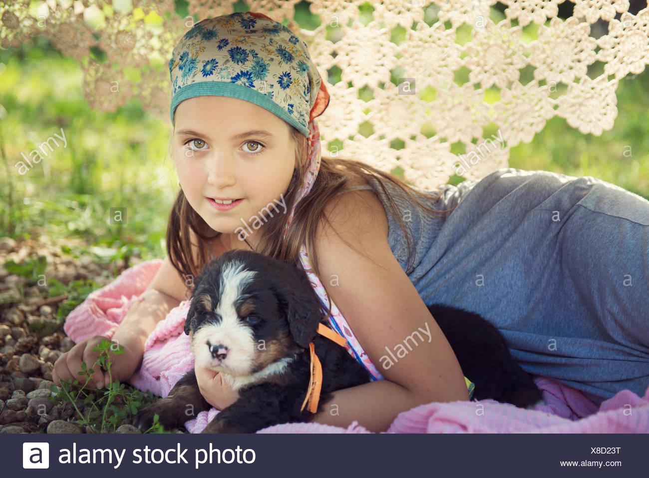 La ragazza che giace sotto un tavolo con un cucciolo Immagini Stock