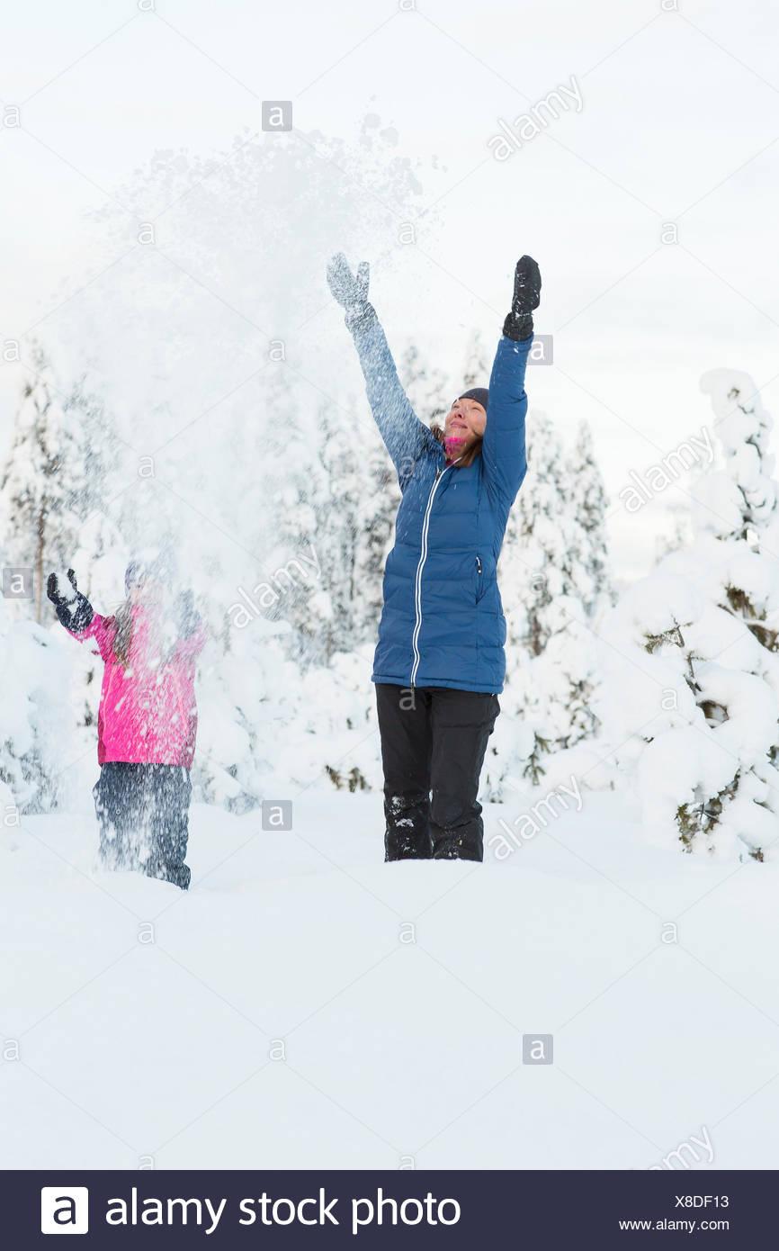 La Svezia, Lapponia, Gallivare, ragazza (4-5) gettando la neve con mamma Immagini Stock