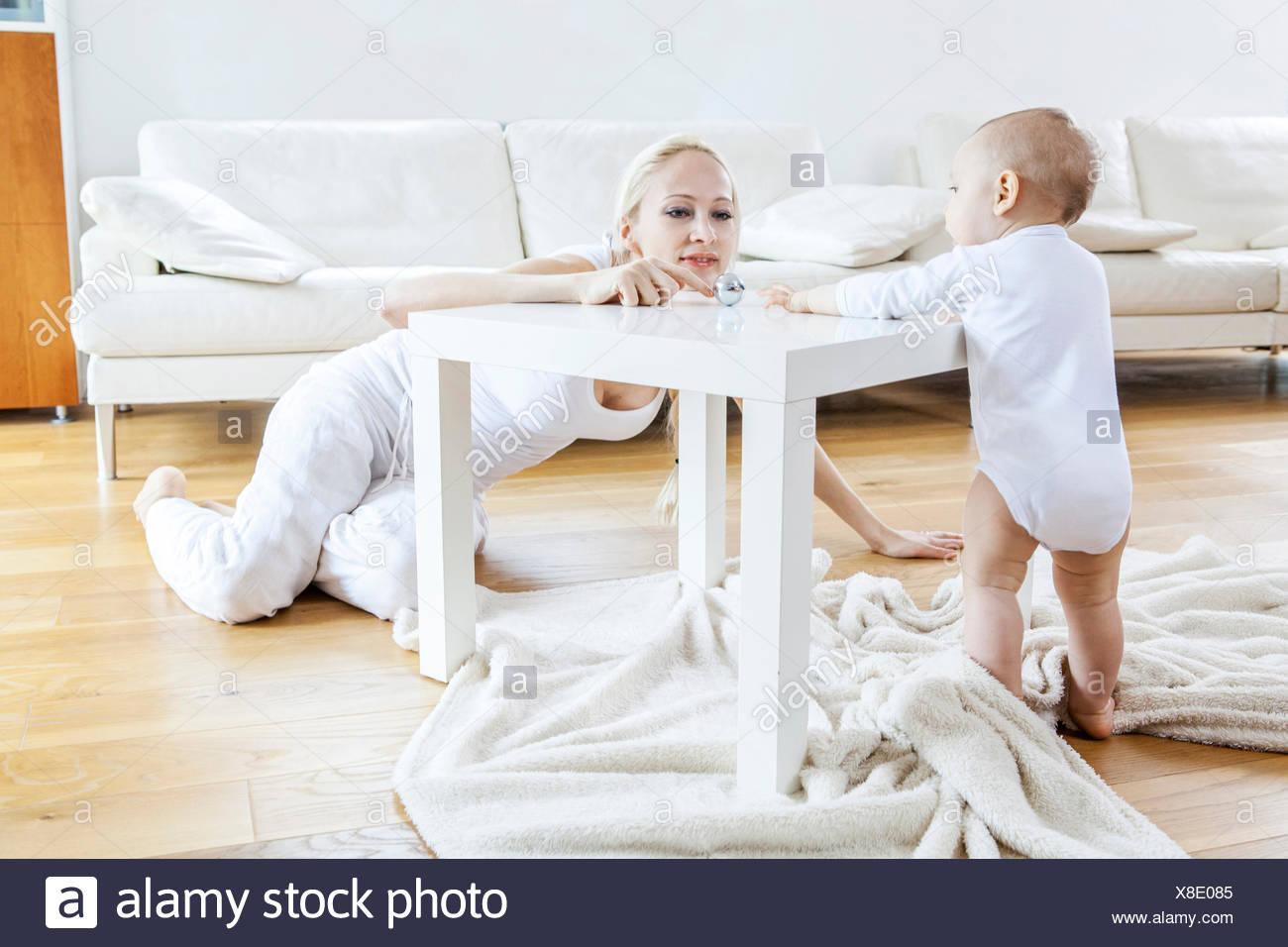 La madre e il bambino giocando in salotto Immagini Stock