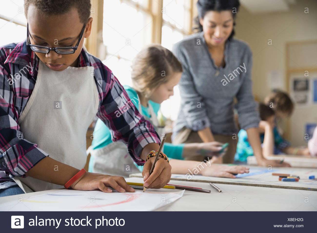 Disegno del ragazzo in classe d'arte Immagini Stock