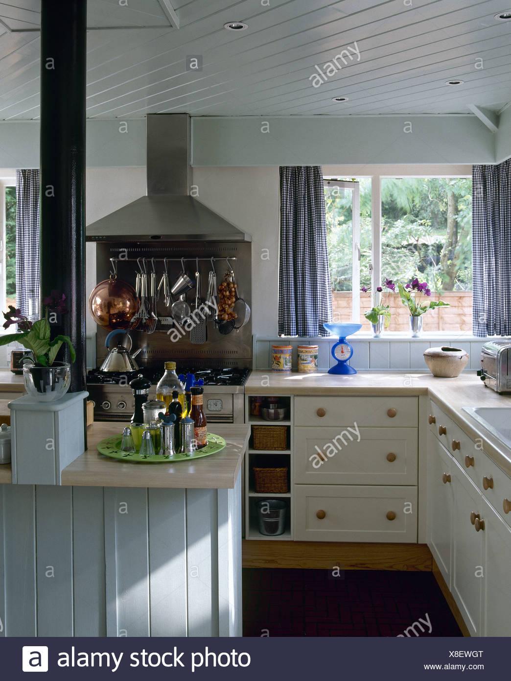 Tende blu sulla finestra in bianco cottage cucina con rack degli ...
