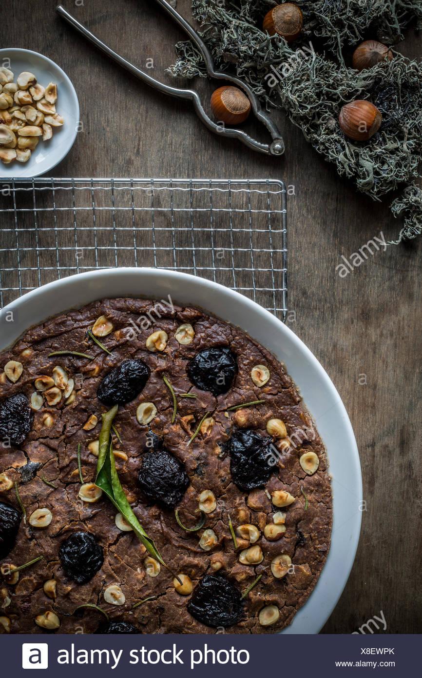 Mediterraneo festosa di farina di castagne torta nel piatto bianco sul raffreddamento per rack su un tavolo di legno alto. Vista dall'alto. Immagini Stock