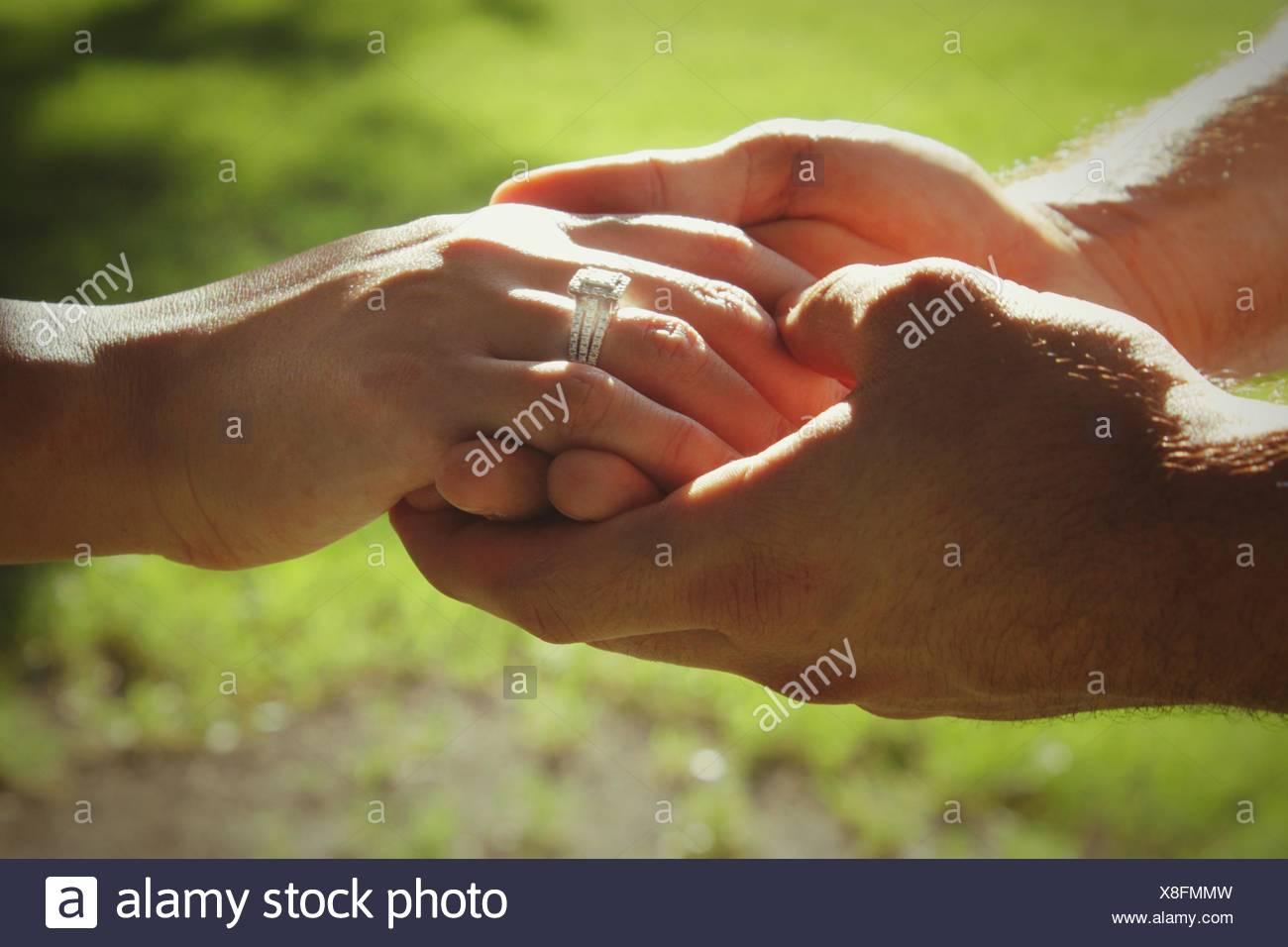 Immagine ritagliata della giovane Holding Hands Immagini Stock