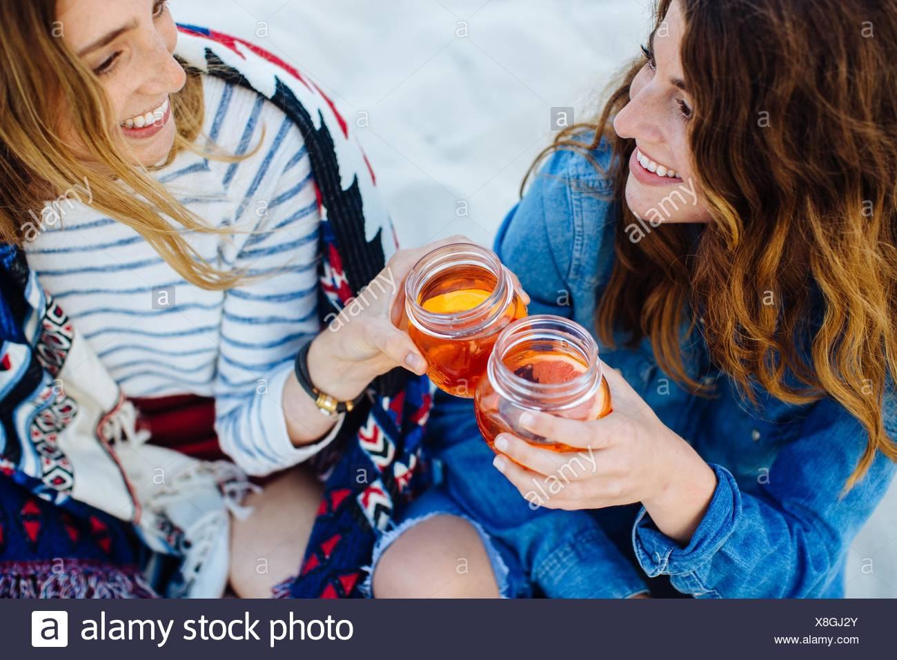 Due giovani amici di sesso femminile la tostatura con jar drink sulla spiaggia Foto Stock