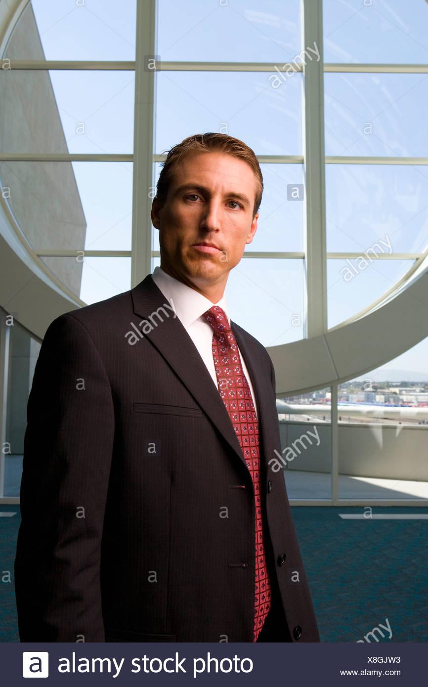 Imprenditore in piedi nella parte anteriore della finestra rotonda Immagini Stock