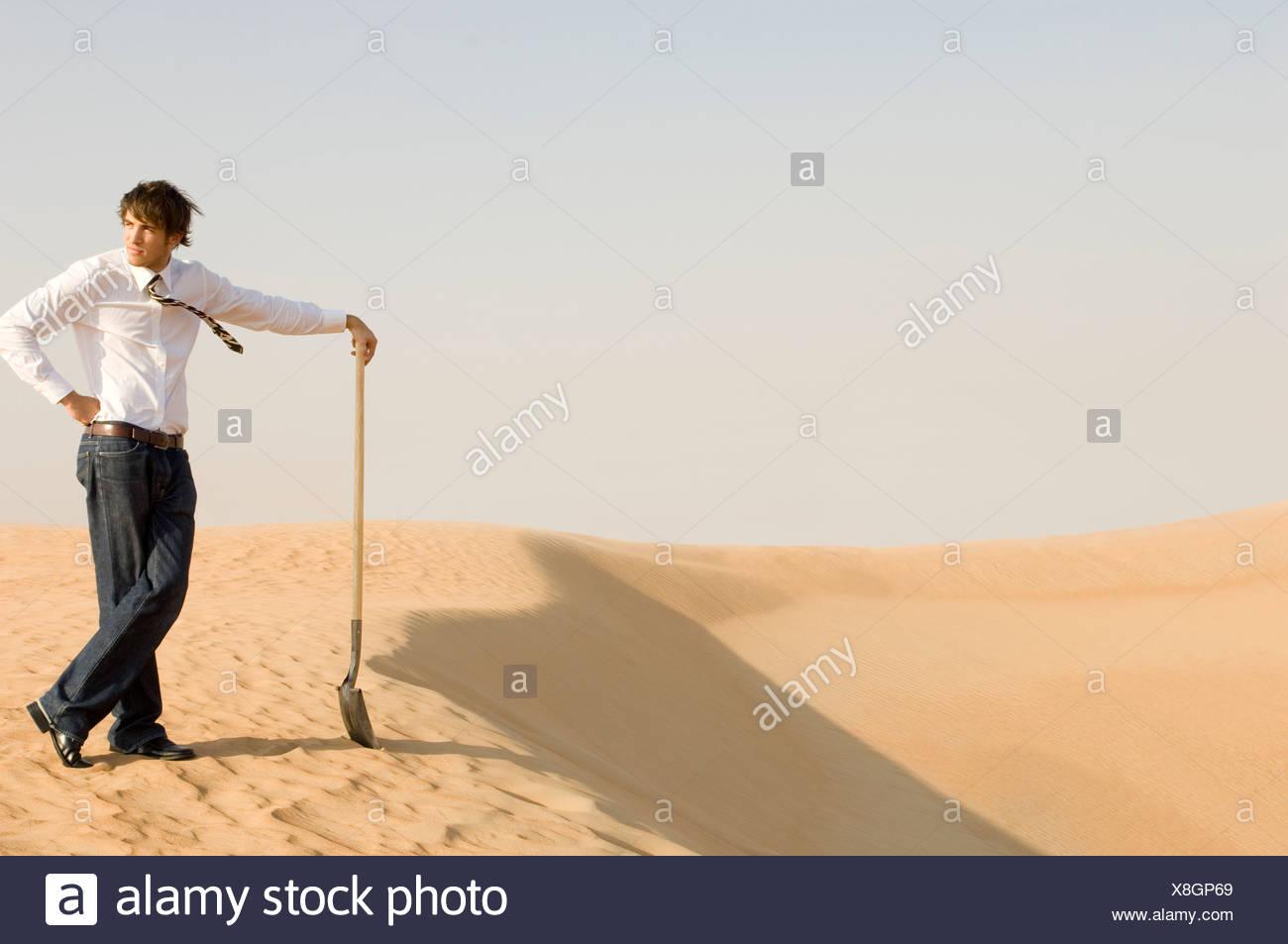 Un giovane uomo in piedi nel deserto con una vanga Immagini Stock