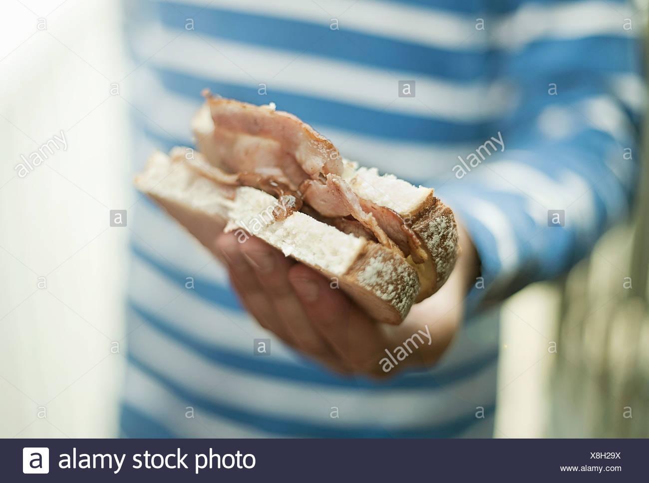 Ragazzo holding sandwich di pancetta Immagini Stock