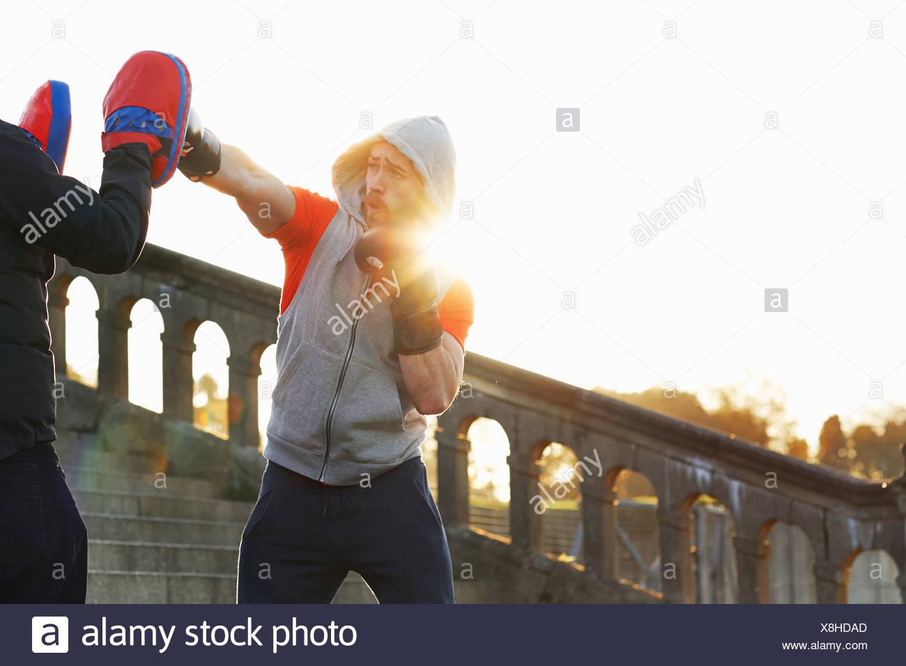 Giovane uomo boxing di formazione con docente Foto Stock